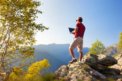 Young caucasian man sitting outdoor on a rock working on a lapto Stock Images