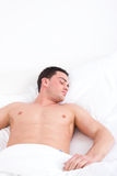 Young caucasian man sleeping in his bed at home Stock Photography