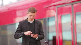 Young caucasian man with smarphone and luggage at station traveling by train. Young man with luggage on the platform waiting for aeroexpress stock video