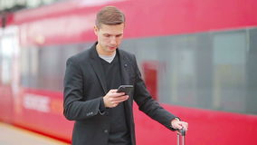 Young caucasian man with smarphone and luggage at station traveling by train. Young man with luggage on the platform waiting for aeroexpress stock footage
