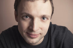 Young Caucasian man smiles, closeup studio portrait Stock Photography