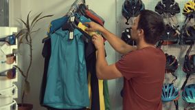 A young Caucasian man is standing near a racks of sports cycling clothes on a hanger in a bicycle store. Choosing a stock video