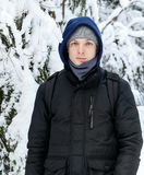 Young Caucasian man stays in winter forest Stock Photography