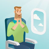 Young caucasian man suffering from aerophobia. Young caucasian man shocked by plane flight in the turbulent area. Frightened airplane passenger sitting in Stock Photography