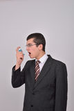 Young caucasian man in suit using an asthma inhaler to handle pr Stock Photography