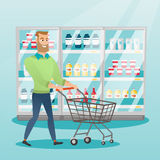 Young caucasian man with supermarket trolley. Young caucasian man pushing an empty supermarket trolley. Man shopping in the supermarket with a trolley. Man Stock Image