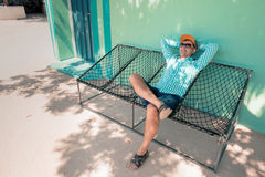 Young caucasian man swinging in a hammock pleasant laziness of weekend morning. Young man with sunglasses relaxing in a hammock in a pleasant laziness of a Stock Photography