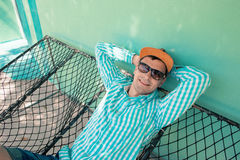 Young caucasian man swinging in a hammock pleasant laziness of weekend morning. Young man with sunglasses relaxing in a hammock in a pleasant laziness of a Stock Photos