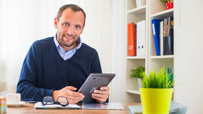 A young caucasian man with tablet in his office. Stock Images