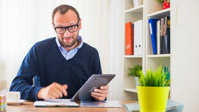A young caucasian man with tablet in his office. Royalty Free Stock Photos