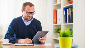 A young caucasian man with tablet in his office. Stock Photos