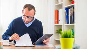 A young caucasian man with tablet in his office. Stock Photo