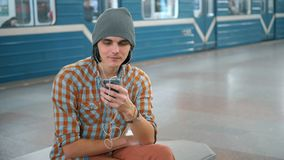 Young caucasian man talking on cellphone on subway platform.  stock footage
