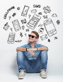 Young caucasian man wear sunglasses while sitting on the floor t Royalty Free Stock Images