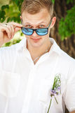 Young Caucasian man wearing sunglasses posing. Attractive happy groom in sunglasses Stock Photos