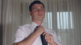 A young caucasian man wears a black tie on a white shirt before work stock video