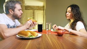 Young caucasian man and woman eating hotdogs and lettuce at home. Junk food versus healthy eating concept. Young caucasian men and women eating hot dogs and royalty free stock photography