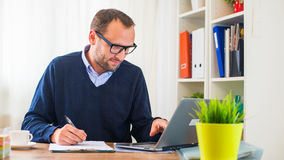 A young caucasian man working on a desk with a laptop. Royalty Free Stock Photo