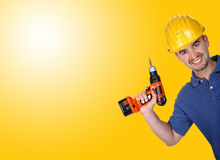 Young caucasian manual worker with  drill. Background Royalty Free Stock Image