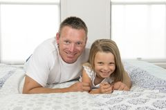 Young man  lying on bed together with adorable 7 years old little girl playing happy at home in family father and daughter love li. Young Caucasian men  lying on Stock Photo