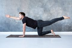 Young caucasian men practices yoga asana chakravakasana stock images