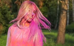 Young caucasian model with fluttering hair in wind playing with. Young caucasian woman with fluttering hair in wind playing with dry paint Holi stock photo