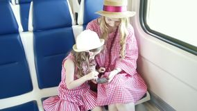 Young caucasian mom and daughter in the arms ride the train and using the mobile phone. Close up stock video footage