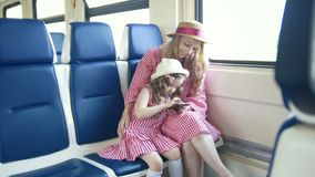 Young caucasian mom and daughter in the arms ride the train and using the mobile phone. Close up stock video
