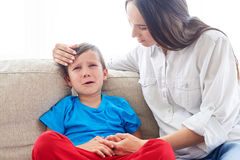 Young Caucasian mom soothing crying son. Close-up shot of young Caucasian mom soothing crying son. Carrying mother sitting with son Royalty Free Stock Photo
