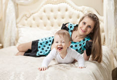 Young Caucasian mother and baby son having fun on bed Royalty Free Stock Photo