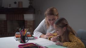 Young Caucasian mother doing homework with her cute daughter. Little smart girl writing in the exercise book, mom stock video footage