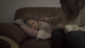 Young caucasian mother sitting with her sick daughter at home. Small pretty girl lying under blanket with fever. Concept. Of health, illness, sickness, common stock footage