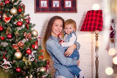 Young caucasian mother standing with little daughter near christmas tree. Young caucasian mother sitting with little daughter near decorated fireplace Royalty Free Stock Images