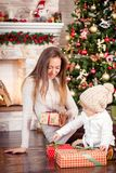 Young caucasian mother sitting with little daughter near decorated fireplace and christmas tree. Young caucasian mother sitting with little daughter near Stock Photos