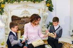 Young caucasian mother sitting with sons and gifts near decorated fireplace. royalty free stock images