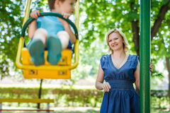 Young caucasian mother with swinging son at playground Stock Photo