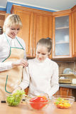 Young Caucasian Mother Teaching Her Teenage Daughter How to Cook Stock Photo