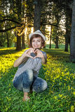 Young caucasian natural woman making heart shape in sunny backli Stock Photo