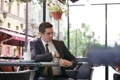 A young businessman came to lunch in a street cafe, he sits at a table and pulls out a purse to pay the bill stock image