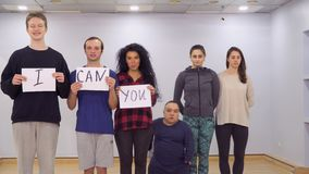 Different young people shows motivation boards and calls to believe in yourself. Young caucasian people approaches to camera one after another with motivation stock video footage