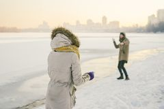 Young Caucasian people in love heterosexual couple have a date in winter near a frozen lake. Active holiday holiday Valentine`s stock photography