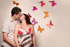 Young caucasian pregnant couple kissing Stock Photos