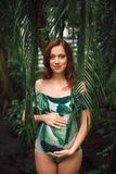 Young caucasian pregnant redhead woman in swimsuit in palm leave. Attractive soon to be mom with a natural beauty and long red hair wearing floral swimsuit stock images
