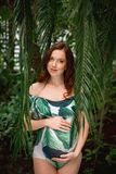 Young caucasian pregnant redhead woman in swimsuit in palm leave. Attractive soon to be mom with a natural beauty and long red hair wearing floral swimsuit stock photos