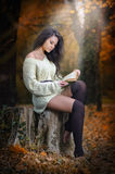 Young Caucasian sensual woman reading a book in a romantic autumn scenery. Portrait of pretty young girl in the forest in autumn. Day. Fashion portrait of a Royalty Free Stock Image