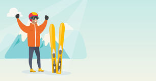 Young caucasian skier standing with raised hands. Caucasian skier standing with raised hands on the background of mountains. Young cheerful skier resting in the Royalty Free Stock Image