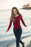Young Caucasian slim woman with messy long hair wearing black jeans and red shirt walking on windy day outdoor on beach. Lifestyle portrait of young Caucasian Stock Photo
