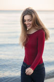 Young Caucasian slim woman with messy long hair wearing black jeans and red shirt walking on windy day outdoor on beach. Lifestyle portrait of young Caucasian Stock Images