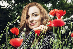 Young caucasian smiling woman with corn poppy flowers, beauty an royalty free stock photo