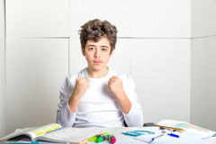 Young Caucasian smooth-skinned boy on homework makes success ges Royalty Free Stock Photography